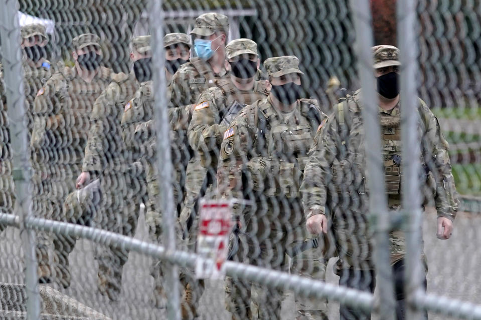 Washington National Guard members walk in formation along a perimeter fence near the Legislative Building, Wednesday, Jan. 20, 2021, at the Capitol in Olympia, Wash. Members of the Guard and Washington State Patrol troopers have been in place all week on the campus providing security against possible protests connected with the inauguration of President Joe Biden and the departure of former President Donald Trump in Washington, D.C. (AP Photo/Ted S. Warren)