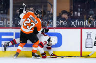 Philadelphia Flyers' Oskar Lindblom (23) and New Jersey Devils' Kevin Bahl (88) collide during the second period of an NHL hockey game, Monday, May 10, 2021, in Philadelphia. (AP Photo/Matt Slocum)