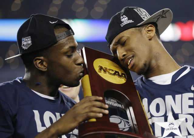 CORRECTS BOATRIGHT TO LASAN KROMAH- Connecticut guard Terrence Samuel, left, and guard Lasan Kromah hold the championship trophy after beating Kentucky 60-54, at the NCAA Final Four tournament college basketball championship game Monday, April 7, 2014, in Arlington, Texas. (AP Photo/David J. Phillip)