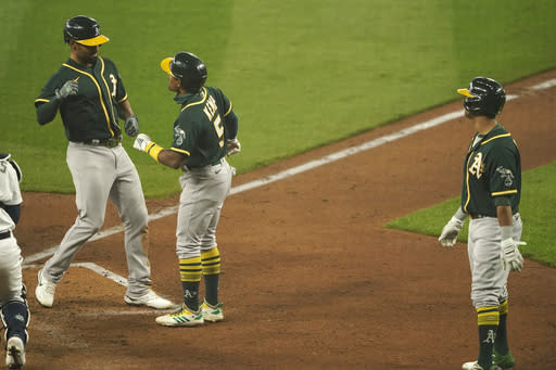 Oakland Athletics' Marcus Semien, left, is greeted by Tony Kemp after hitting a three-run home run to score Kemp and Khris Davis, right, during the fourth inning of the first baseball game against the Seattle Mariners in a doubleheader, Monday, Sept. 14, 2020, in Seattle. (AP Photo/Ted S. Warren)