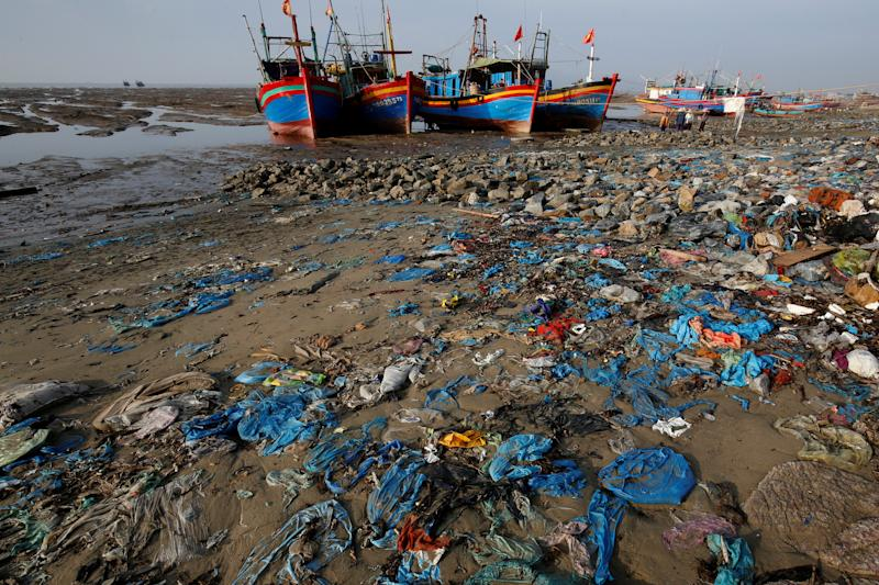 Fishermen boats are seen at a beach covered with plastic waste in Thanh Hoa province, Vietnam. (Photo: Nguyen Huy Kham/Reuters)