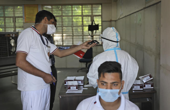 A Delhi police volunteer holds a mobile phone for a health worker as she takes an urgent call during testing for COVID-19 in New Delhi, India, Saturday, Oct. 3, 2020. India has crossed 100,000 confirmed COVID-19 deaths on Saturday, putting the country's toll at nearly 10% of the global fatalities and behind only the United States and Brazil. (AP Photo/Manish Swarup)