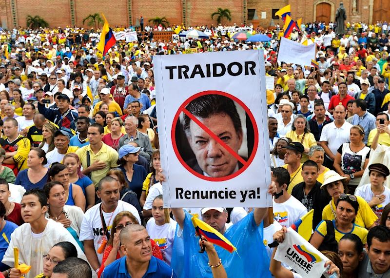 """People hold a picture of Colombian President Juan Manuel Santos reading """"Traitor. Resign now"""" during a protest against his government's peace process with the FARC guerrillas (AFP Photo/Luis Robayo)"""