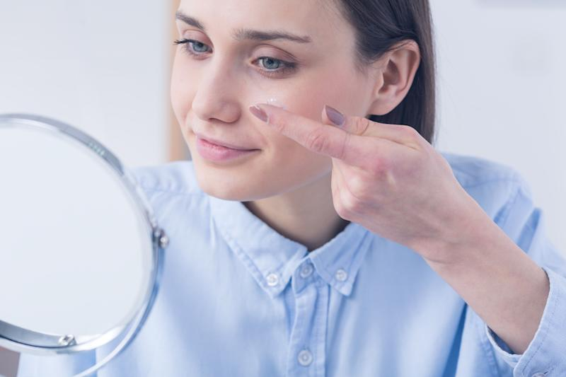 Woman inserting contact lens, sitting in front of a mirror
