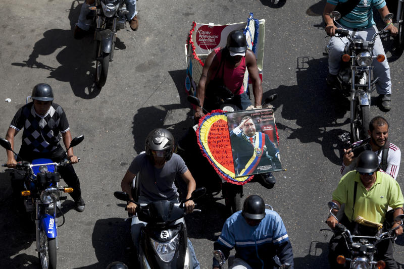 A motorcyclist carries a poster of Venezuela's late President Hugo Chavez during a protest against a proposed nighttime curfew for two-wheelers in Caracas, Venezuela, Friday, Jan. 31, 2014. President Nicolas Maduro's government this month lent its support to proposals to ban motorcycles from circulating at night, arguing that the vehicles are used to carry out murders and kidnappings that have proliferated recently. (AP Photo/Alejandro Cegarra)