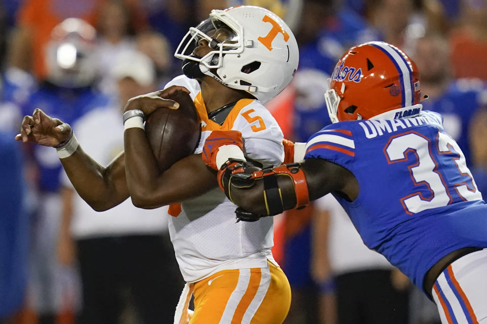 Tennessee quarterback Hendon Hooker (5) is stopped by Florida defensive lineman Princely Umanmielen (33) during the first half of an NCAA college football game, Saturday, Sept. 25, 2021, in Gainesville, Fla. (AP Photo/John Raoux)