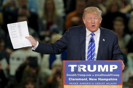 U.S. Republican presidential candidate Donald Trump holds up his notes of a recent poll at a campaign rally in Claremont