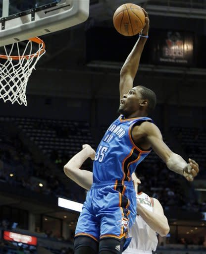 Oklahoma City Thunders' Kevin Durant dunks against Milwaukee Bucks' Ersan Ilyasova, right, during the first half of an NBA basketball game Monday, April 9, 2012, in Milwaukee. (AP Photo/Jeffrey Phelps)