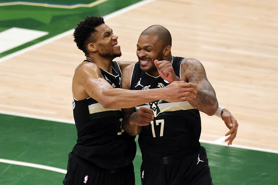 Giannis Antetokounmpo celebrates with P.J. Tucker in the final seconds of the Bucks' NBA Finals-clinching win over the Phoenix Suns on Tuesday. (Jonathan Daniel/Getty Images)