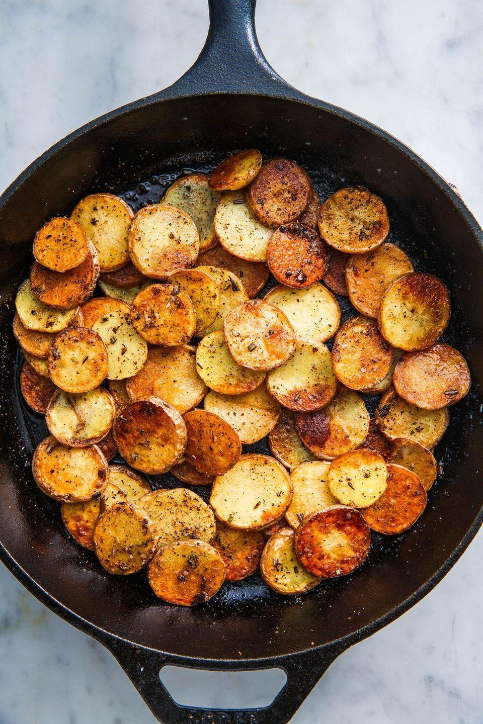 """<p>A lot of pan fried potatoes take wayyy longer than they should. You're first asked to boil the potatoes then chop and fry them. We can hardly think of anything more annoying. Especially if you're feeling lazy, hungover, or rushed—or all of the above. The truth is, you don't need to pre-cook the potatoes at all. You just need to slice 'em thin and choose the best oils...plural!</p><p>Get the <a href=""""https://www.delish.com/uk/cooking/recipes/a28786092/pan-fried-potatoes/"""" rel=""""nofollow noopener"""" target=""""_blank"""" data-ylk=""""slk:Pan Fried Potatoes"""" class=""""link rapid-noclick-resp"""">Pan Fried Potatoes</a> recipe.</p>"""