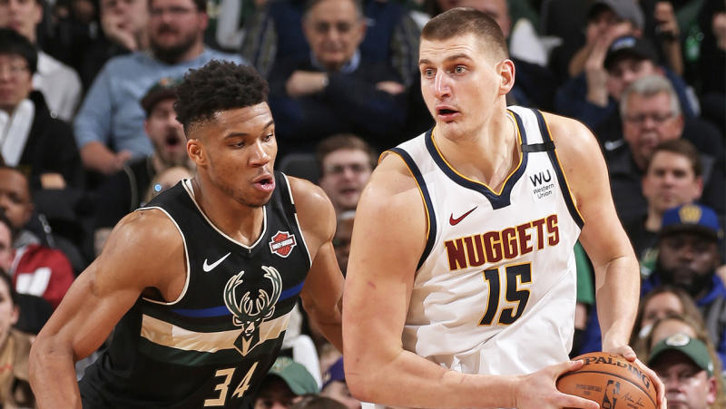 Nikola Jokic looks to pass the ball as Giannis Antetokounmpo defends him.