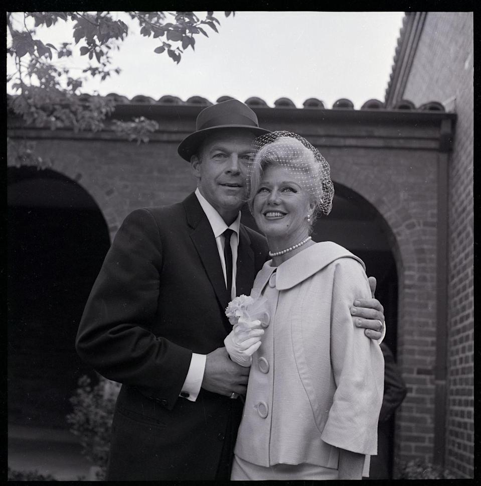 <p>Ginger Rogers married her fifth and final husband, William Marshall, in 1961. The bride wore a wide collared jacket with a net fascinator. </p>