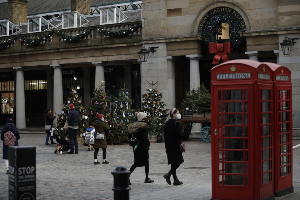People wearing face masks walk and stand backdropped by Christmas trees in Covent Garden, during England's second coronavirus lockdown in London, Thursday, Nov. 26, 2020. As Christmas approaches, most people in England will continue to face tight restrictions on socializing and business after a nationwide lockdown ends next week, the government announced Thursday. (AP Photo/Matt Dunham)