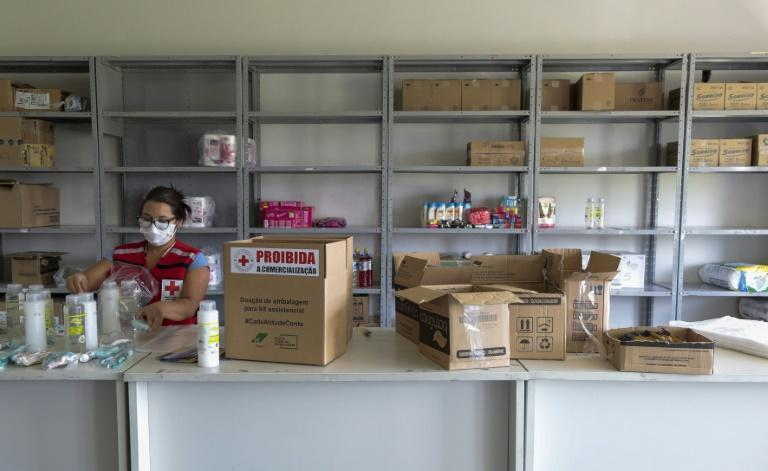 A volunteer from the Sao Paulo Red Cross prepares a kit with sanitation products to be donated to families affected by the Covid-19 pandemic in Sao Paulo, Brazil, on March 23, 2021
