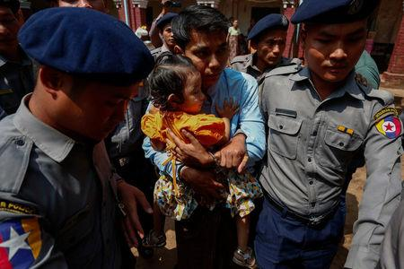 Detained Reuters journalist Kyaw Soe Oo holds his daughter as he is escorted by police while arriving for a court hearing after a lunch break in Yangon, Myanmar February 21, 2018. REUTERS/Stringer