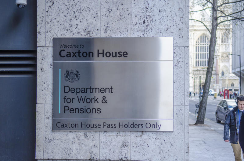Exterior signage of UK government building with people walking past