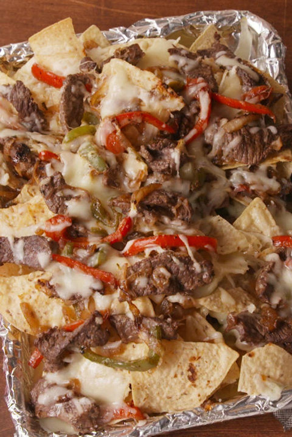 """<p>Step up your nacho game this year by adding a delicious Philly cheesesteak twist — just add steak, peppers, and onions, along with the best cheeses.</p><p><em><a href=""""http://www.delish.com/cooking/recipe-ideas/recipes/a51879/philly-cheesesteak-nachos-recipe/"""" rel=""""nofollow noopener"""" target=""""_blank"""" data-ylk=""""slk:Get the recipe from Delish »"""" class=""""link rapid-noclick-resp"""">Get the recipe from Delish » </a></em></p><p><strong>RELATED: </strong><a href=""""https://www.goodhousekeeping.com/health/diet-nutrition/g28829538/healthiest-cheese/"""" rel=""""nofollow noopener"""" target=""""_blank"""" data-ylk=""""slk:The Healthiest Cheeses You Can Buy, According to a Registered Dietitian"""" class=""""link rapid-noclick-resp"""">The Healthiest Cheeses You Can Buy, According to a Registered Dietitian</a></p>"""