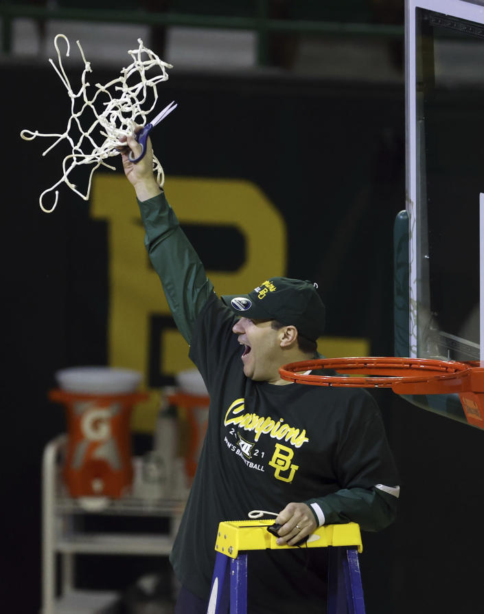 Baylor head coach Scott Drew holds up the netting as they celebrate their Big 12 championship after their game NCAA college basketball game against Texas Tech Sunday, March 7, 2021, in Waco, Texas. (AP Photo/Jerry Larson)