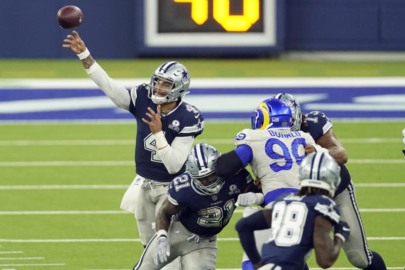 Dallas Cowboys quarterback Dak Prescott, left, throws behind a block by Ezekiel Elliott (21) during the second half of an NFL football game against the Los Angeles Rams Sunday, Sept. 13, 2020, in Inglewood, Calif. (AP Photo/Ashley Landis)