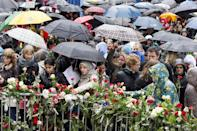 """People lays flowers near the entrance the courthouse in Oslo where Anders Behring Breivik is standing trial Thursday April 26, 2012. Nearly 40,000 people who turned up in poor weather at the Youngstorget Square in Oslo to participate in the singing of """"Barn av Regnbuen"""" """"Children of the Rainbow"""" . The song which was a hit of Norwegian folk singer Lillebjoern Nilsen several decades ago, has become a signature tune for the victims of the July 22, 2011 bombing and shooting massacre that killed 77 people. (AP Photo/Heiko Junge / NTB scanpix) NORWAY OUT"""