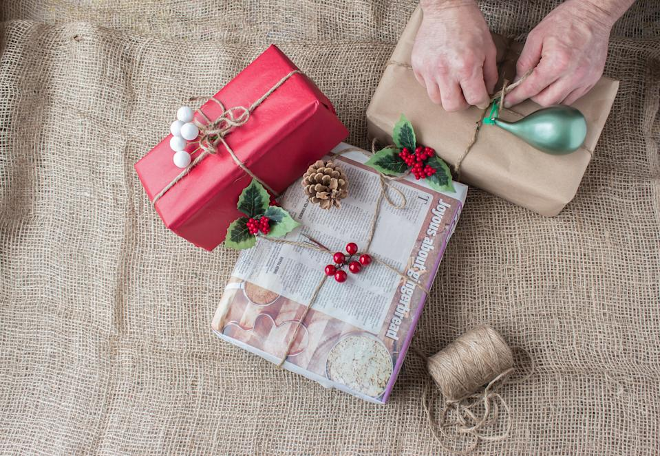 very rustic country christmas image with man's hands wrapping christmas gift with brown paper and tying with baler twine with another gift wrapped in news paper with ginger bread story on it lying on a burlap background