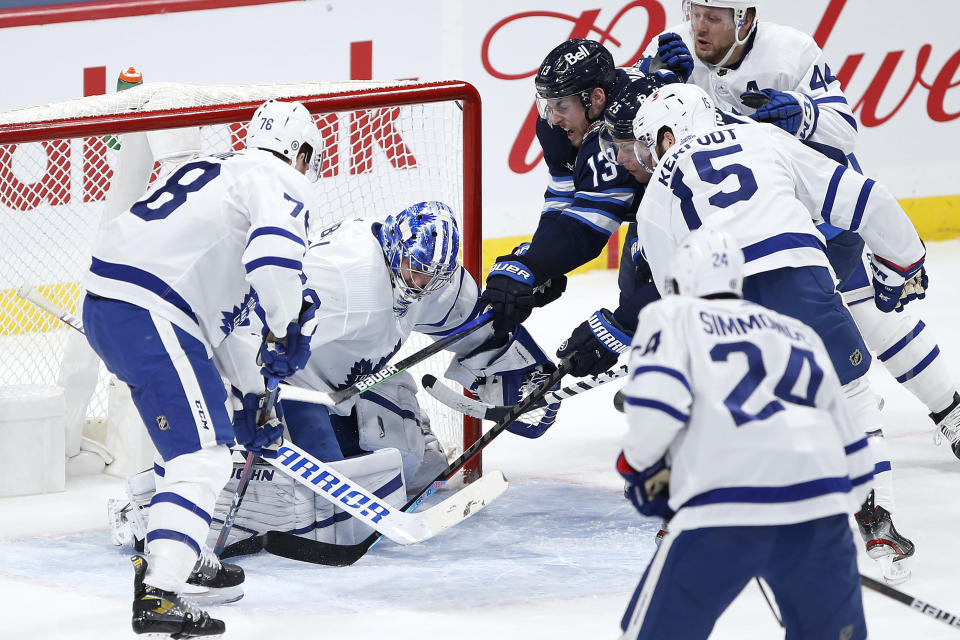Winnipeg Jets' Pierre-Luc Dubois (13) and Paul Stastny (25) scramble for the puck in front of Toronto Maple Leafs goaltender Jack Campbell (36) as TJ Brodie (78) and Alexander Kerfoot (15) defend during the first period of an NHL hockey game Thursday, April 22, 2021, in Winnipeg, Manitoba. (John Woods/The Canadian Press via AP)