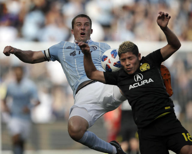 Sporting Kansas City defender Matt Besler, back, kicks the ball over Columbus Crew midfielder Cristian Martinez (18) during the first half of an MLS soccer match in Kansas City, Kan., Sunday, May 27, 2018. (AP Photo/Orlin Wagner)