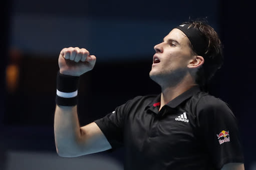 Dominic Thiem of Austria celebrates winning his singles tennis match against Rafael Nadal of Spain at the ATP World Finals tennis tournament at the O2 arena in London, Tuesday, Nov. 17, 2020. (AP Photo/Frank Augstein)