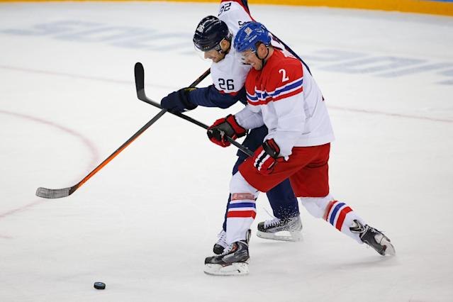 Slovakia forward Michal Handzus (26) and Czech Republic defenseman Marek Zidlicky (2) battle for control of the puck during the first period of the 2014 Winter Olympics men's ice hockey game at Shayba Arena, Tuesday, Feb. 18, 2014, in Sochi, Russia. (AP Photo/Petr David Josek)