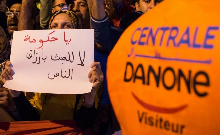 A demonstrator holds a sign as employees of the company Centrale Danone, a subsidiary of French multinational Danone, protest in front the parliament in Rabat on June 5, 2018, against the boycott of the brand in Morocco