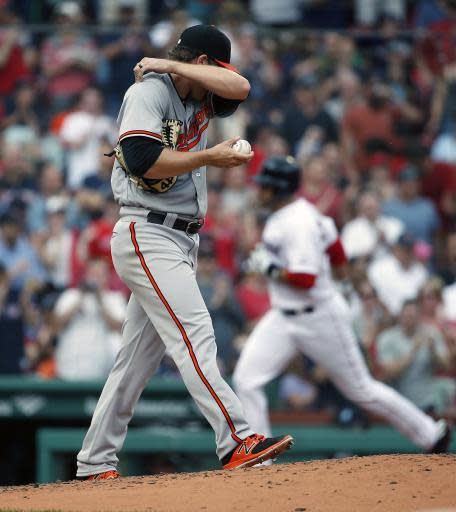 Baltimore Orioles' David Hess walks on the mound as Boston Red Sox's J.D. Martinez, right, rounds third base on his two-run home run during the fifth inning of a baseball game in Boston, Sunday, May 20, 2018. (AP Photo/Michael Dwyer)