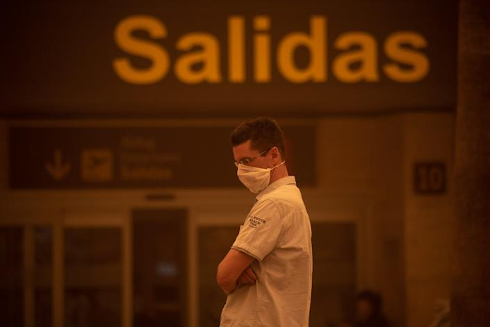 A man wearing a mask stands outside Tenerife SouthReina Sofia Airport during a sandstorm on February 23, 2020 on the Canary Island of Tenerife.