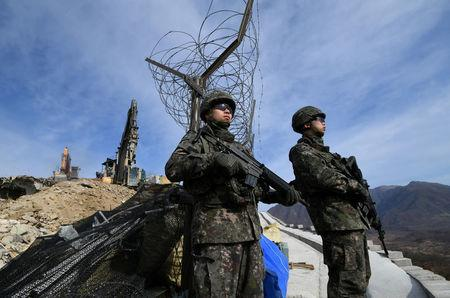 FILE PHOTO: South Korean soldiers stand guard as construction equipment destroy a guard post in the Demilitarized Zone dividing the two Koreas in Cheorwon
