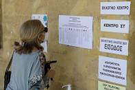 A woman looks at a voting list at a polling station during parliamentary elections in Nicosia