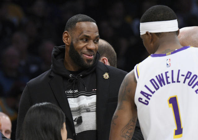 Los Angeles Lakers guard LeBron James, left, talks with guard Kentavious Caldwell-Pope during the first half of an NBA basketball game against the Denver Nuggets Sunday, Dec. 22, 2019, in Los Angeles. LeBron James sat out the game because of a thoracic muscle strain. (AP Photo/Michael Owen Baker)
