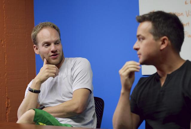 In this photo from Aug. 14, 2014, David Graff, CEO of Hudl, left, speaks to John Wirtz, Chief Product Officer, in Lincoln, Neb. Hudl is a software company that has developed a way to immediately get game film to coaches after games and break down and separate different plays by type. (AP Photo/Nati Harnik)