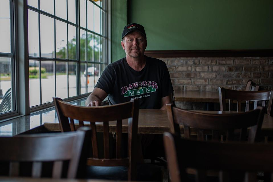 """Dawson's on Main owner Chris Hill sits at an empty table inside his Speedway, Ind., restaurant on Thursday, May 14, 2020. """"Our servers have been here for a long time and they become family,"""" he said. """"When you don't see them it's disappointing."""" Hill was able to partly keep his staff but others had to be let go due to money issues caused by the coronavirus pandemic. """"That's the great unknown moving forward,"""" he said. """"How much staff can we bring back? How much staff should we bring back and with outdoor, we don't have the ability to put up tents here. You have to kind of look to the sky to see what that's going to do to staff appropriately."""""""