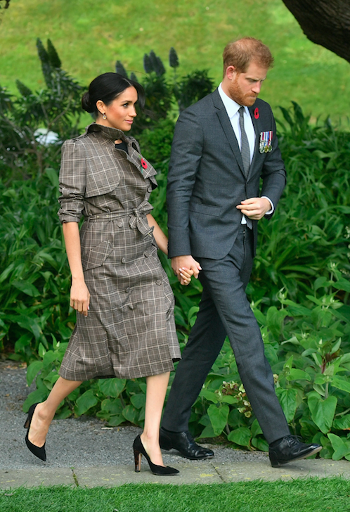 <p>Meghan took the time in the air to change into a black ASOS maternity dress, brown Karen Walker trench coat and black Sarah Flint heels. Photo: Getty </p>