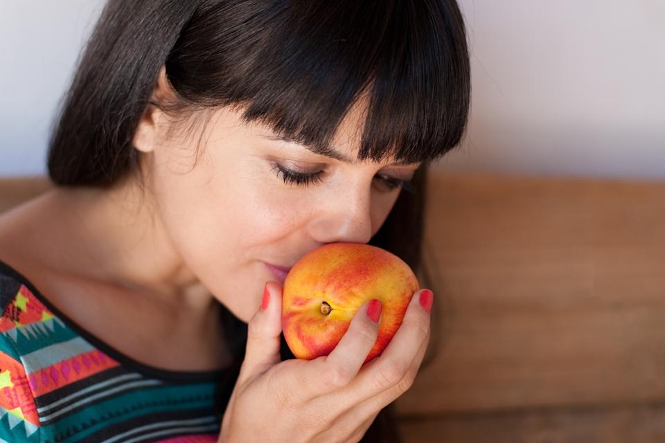Portrait of young woman smelling a fresh and sweet nectarine