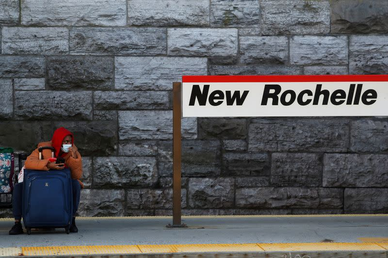 FILE PHOTO: A woman wearing a protective face mask sits, as the global outbreak of the coronavirus disease (COVID-19) continues, with luggage at the Metro-North Railroad and Amtrak train station in New Rochelle, New York