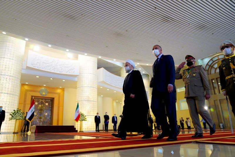 FILE PHOTO: Iranian President Hassan Rouhani welcomes Iraqi Prime Minister Mustafa al-Kadhimi as they wear protective masks, in Tehran