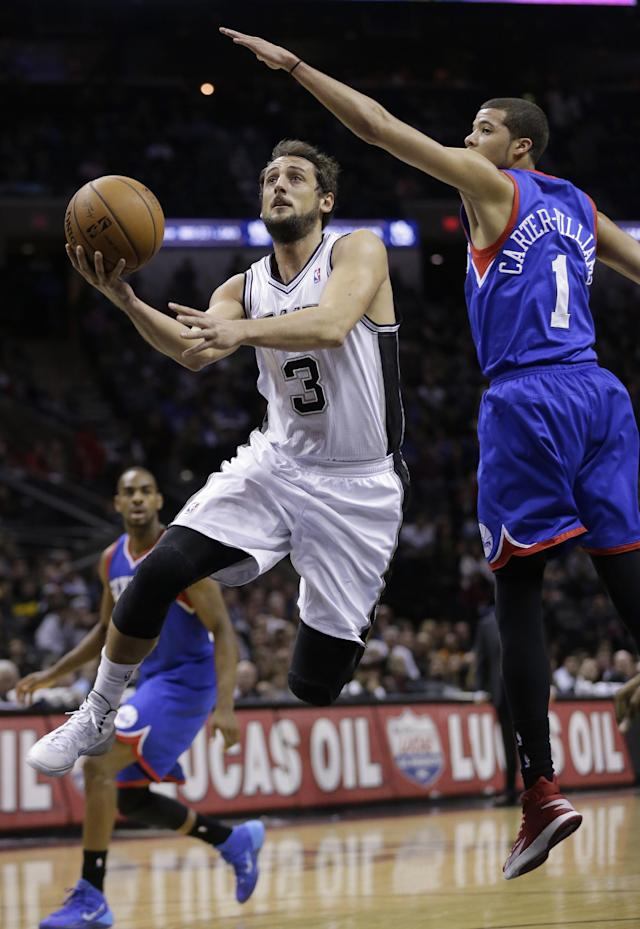 San Antonio Spurs' Marco Belinelli (3), of Italy, drives around 76ers' Michael Carter-Williams (1) during the first half of an NBA basketball game, Monday, March 24, 2014, in San Antonio. (AP Photo/Eric Gay)