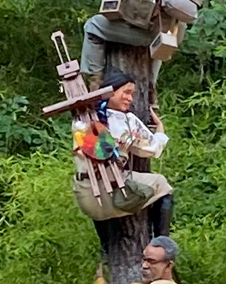 A woman wearing a painting easel on her back