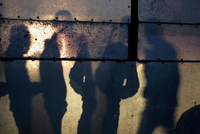 <p>Shadows cast by Palestinians waiting to cross into Egypt through Rafah border crossing between Gaza Strip and Egypt in the southern Gaza Strip, Feb. 7, 2018. (Photo: Mohammed Saber/EPA-EFE/REX/Shutterstock) </p>