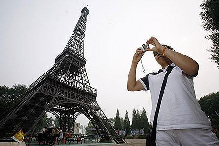 CHINA: A Chinese visitor takes photographs near a replica of the Eiffel Tower at Beijing World Park, one of the three designated 'protest parks', in Beijing July 25, 2008.