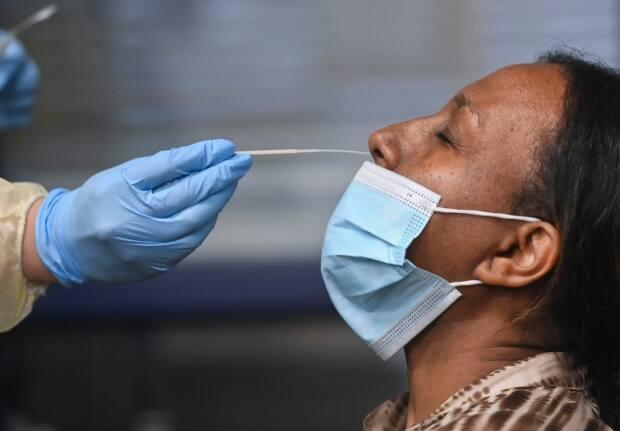 A health-care worker tests a woman at a pop-up COVID-19 assessment centre at the Angela James Arena in Toronto on May 19, 2021.  (Nathan Denette/The Canadian Press - image credit)