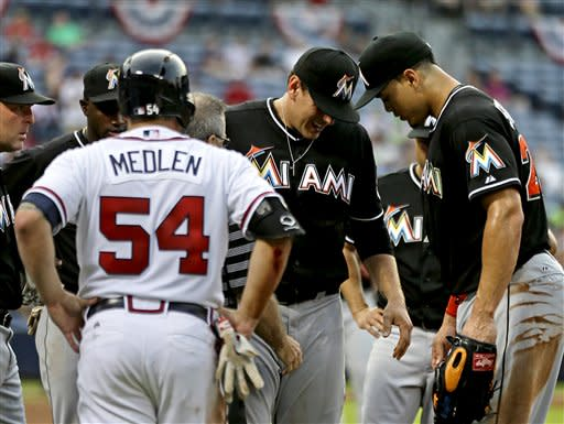 Miami Marlins first baseman Logan Morrison, second from right, gets up after being knocked over in a collision with Atlanta Braves' Kris Medlen, left, after Medlen singled on a bunt ground ball to score teammate Chris Johnson, in the third inning of a baseball game, Tuesday, July 2, 2013, in Atlanta. (AP Photo/David Goldman)