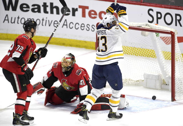 Buffalo Sabres' Nicholas Baptiste (13) celebrates the goal of his teammate Marco Scandella, not shown, as the puck bounces in the net behind Ottawa Senators goaltender Craig Anderson (41) and Thomas Chabot (72) during first period NHL hockey action in Ottawa, Thursday, March 8, 2018. (Justin Tang/The Canadian Press via AP)