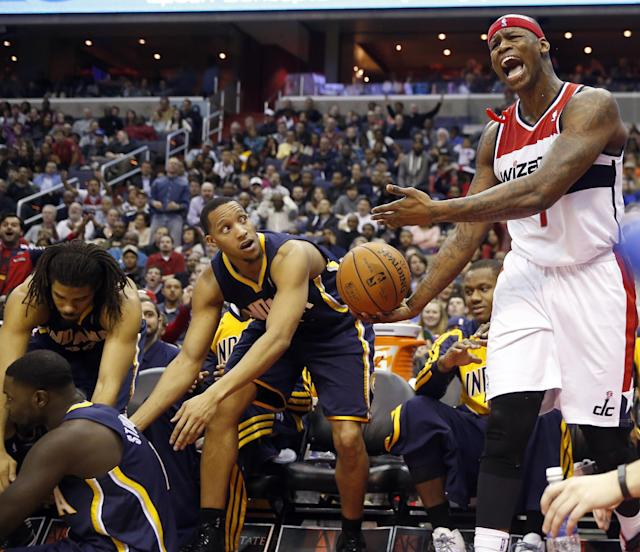 Washington Wizards forward Al Harrington (7) gestures after a collision as Indiana Pacers forward Paul George, center, moves to help up a teammate in the second half of an NBA basketball game on Friday, March 28, 2014, in Washington. The Wizards won 91-78. (AP Photo/Alex Brandon)