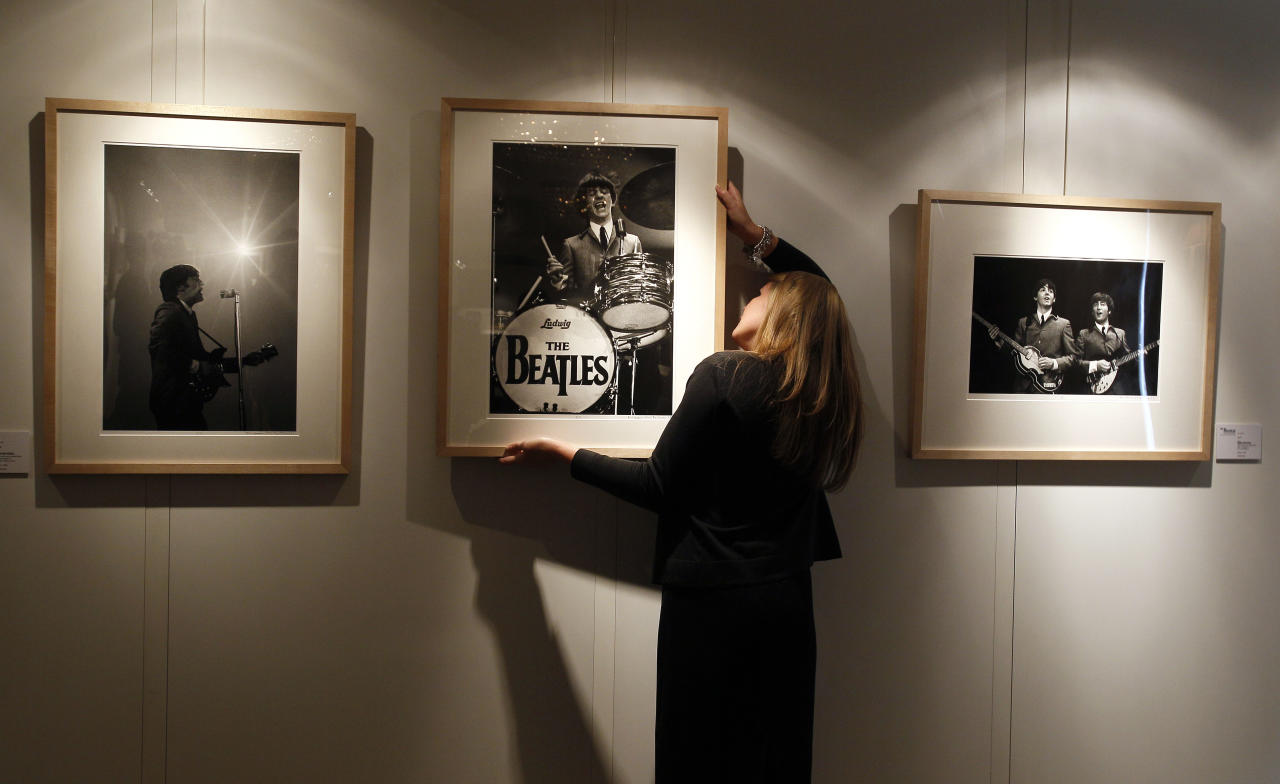 A Christie's employee hangs Mike Mitchell's photograph of The Beatles where his collection is being exhibited at a hotel in London, Friday, June 10, 2011. The previously unseen photographs by US photographer Mike Mitchell were taken during the1964 visit to America. The collection of 50 pictures entitled 'Beatles Illuminated' is expected to realise 100,000 US Dollars (61,500 pounds) when they are auctioned in New York on July 20. (AP Photo/Kirsty Wigglesworth)